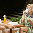 Attractive couple having breakfast by the swimming pool in an exotic garden while on vacations. — Stock Photo #21100391