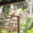 Professional man leaning on a wooden banister and speaking on a cell phone — Foto de Stock   #21100431