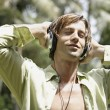 Happy man listening to music with headphones in a tropical garden. — Foto de Stock