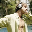 Side view of a young man on vacation, listening to musing with headphones — Stock Photo #21100595