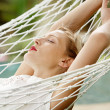 Young attractive woman with red lipstick laying down on a white hammock — Stok fotoğraf