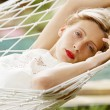 Young attractive woman laying and relaxing on a white hammock — Stock Photo
