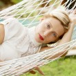 Attractive woman laying and relaxing on a white hammock — Stok fotoğraf
