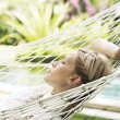 Portrait of an attractive blonde woman laying down on a hammock  — Stock Photo