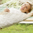 Young woman laying and relaxing on a white hammock — Stock Photo #21100733