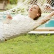 Royalty-Free Stock Photo: Young woman laying and relaxing on a white hammock
