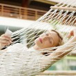 Attractive young woman laying down and relaxing on a white hammock — Stockfoto
