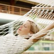 Attractive woman using an mp4 player to listen to music with headphones while laying in a hammock — Stock Photo #21100755