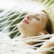 Attractive blonde womlaying down on hammock — Stok Fotoğraf #21100763