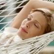 Young beautiful woman laying down on a hammock — Stock Photo #21100773
