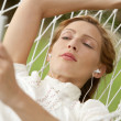 Young beautiful woman laying down on a hammock — Stockfoto