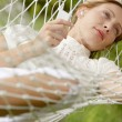 Young beautiful woman laying down on a hammock — Stock Photo