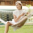Attractive young woman listening to music while sitting on a hammock — Stock Photo #21100807