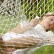 Royalty-Free Stock Photo: Young beautiful woman laying down on a hammock while on vacations