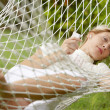 Young beautiful woman laying down on a hammock while on vacations — Stock Photo #21100813