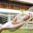 Young woman listening to music while sitting on a hammock — Stock Photo
