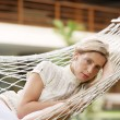 Attractive young woman listening to music while sitting on a hammock — Foto Stock