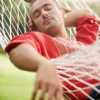Stock Photo: Young attractive man laying down on a net hammock