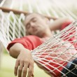 Detail view of a man's relaxed hand while he sleeps on a hammock in the garden. - Stock Photo