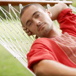 Attractive young man laying down on a hammock — Stock Photo