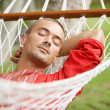 Stock Photo: Attractive man sleeping on a hammock