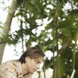 Young man using a laptop computer in a tropical garden — Stock Photo
