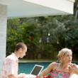 Sophisticated couple relaxing by the swimming pool of their holiday home garden — Stock Photo #21100989