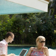 Stock Photo: Young couple lounging by pool in garden, using technology and reading magazine.