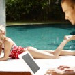 Stock Photo: Sophisticated young couple relaxing by swimming pool