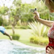 Woman using a video camera to film a man diving into a swimming pool — Stock Photo