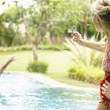 Woman using a video camera to film a man diving into a swimming pool in the garden. — Stock Photo