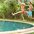 Young fun couple jumping into a tropical swimming pool - Stockfoto