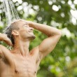 Portrait of a young attractive man having a shower in a tropical garden — Stock Photo