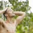 Young man under an outdoor shower with water splashing on his head — Stock Photo