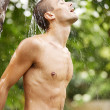Stock Photo: Attractive young man enjoying a shower in a tropical garden with palm trees