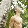 Stock Photo: Young man under an outdoor shower with water splashing on his head