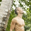 Young man under an outdoor shower with water splashing on his head — Stock Photo #21101123