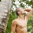 Attractive young man enjoying a shower in a tropical garden with palm trees — Stock Photo