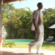 Blurred figure of man walking along an exotic garden with swimming pool. — Stock Photo #21101345