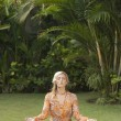 Young blonde woman in yoga position surrounded by nature. - Stock Photo