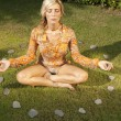 Woman doing yoga inside a circle of stones, outdoors. - Stock Photo