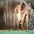 Water splashing onto a young couple near a tropical swimming pool. — Stock Photo