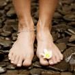 Young woman's feet standing on black natural stones — Стоковая фотография