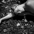 Attractive woman laying down on natural stones - Stok fotoğraf