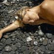 Young woman laying down nude on a bed of black stones outdoors. - Stock Photo