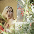 Blonde woman seen through the leaves of a tropical plant. — Stock Photo