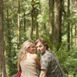 Man and woman sitting down in a tropical forest. — Stock Photo