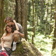 Couple being affectionate while sitting down in a tropical forest. — Stock Photo #21103339