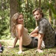 Photo: Couple sitting down in a tropical forest.