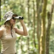 Young woman using binoculars in the rainforest. — Stockfoto